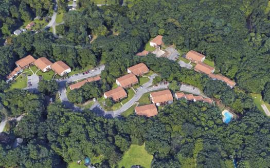 Aerial view of condominium complex with pool