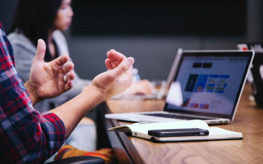 Expressive hands during meeting with computer in background
