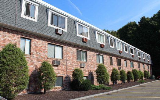 Brick condominium building with mulch and trees in Danbury, Connecticut